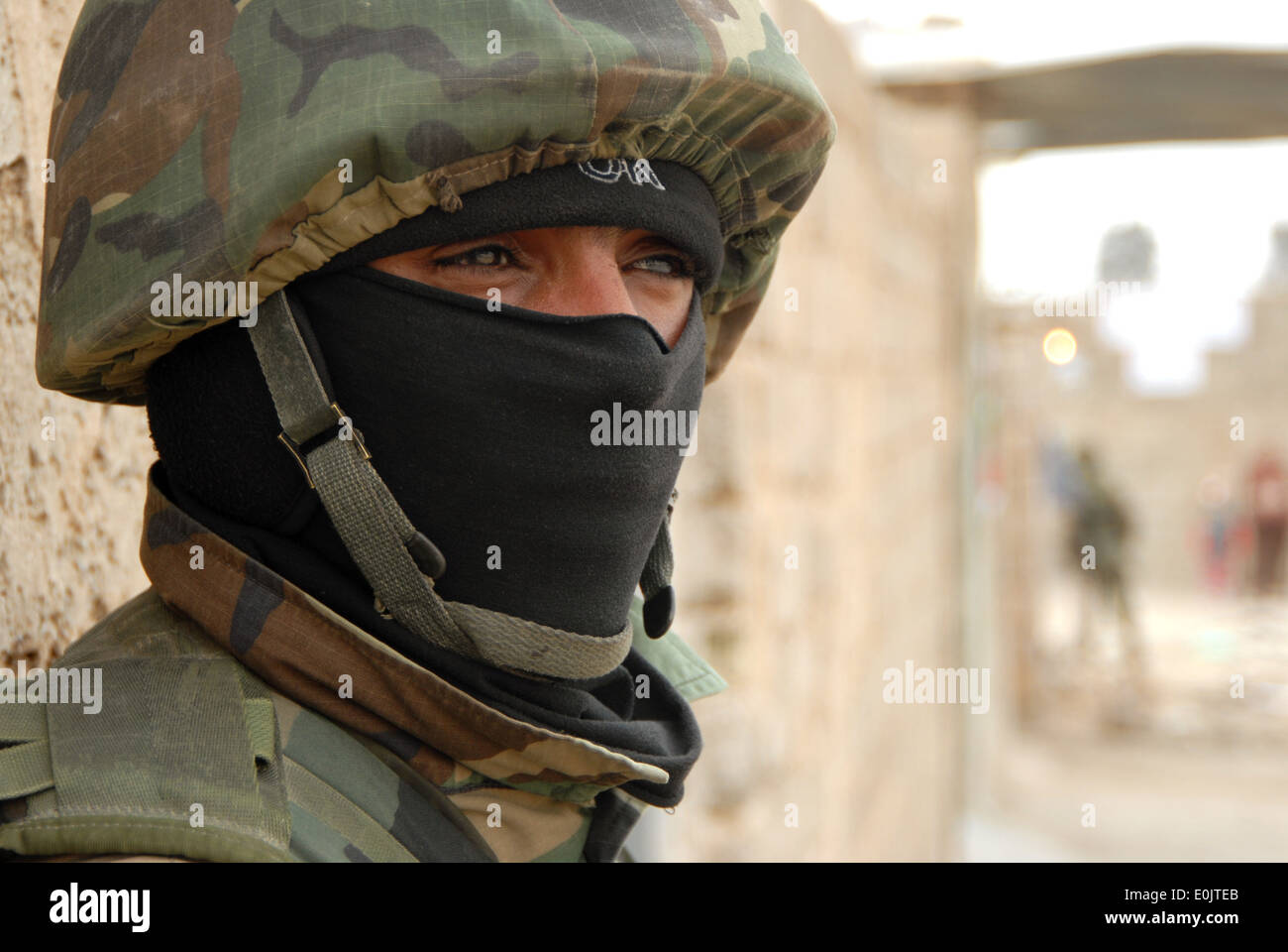 An Iraqi army soldier with the Emergency Unit secures the area while stopped during a joint neighborhood patrol with U.S. Army - Stock Image