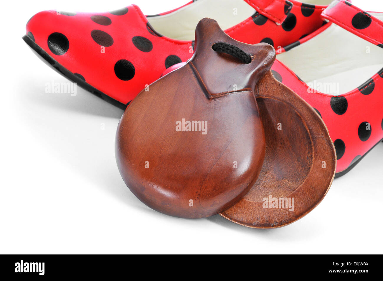 spanish castanets and typical dot-patterned red flamenco shoes, on a white background - Stock Image
