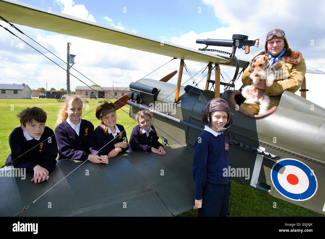 Stow Maries Aerodrome, UK. 14th May, 2014. Commemoration of Edgar Roberts WWI Royal Flying Corps Pilot accompanied on his fighter pilot missions by his terrier Mersea Mick Picture shows pupils (l-r) Ben Rumble, Zoe Clegg, Alannah Murrel, Amber Jones and Cameron Hope from the Mersea Island School visiting Stow Maries Aerodrome gathered around a SE5a replica WWI aeorplane alongside pilot (Trevor Poole). Credit:  Clickpics/Alamy Live News - Stock Image