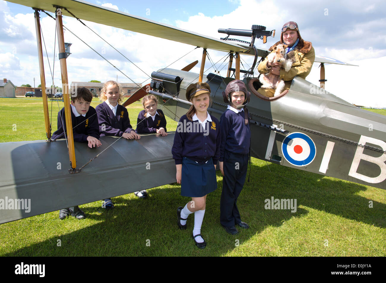 Stow Maries Aerodrome, UK. 14th May, 2014. Commemoration of Edgar Roberts WWI Royal Flying Corps Pilot accompanied on his fighter pilot missions by his terrier Mersea Mick. Picture shows pupils (l-r) Ben Rumble, Zoe Clegg, Amber Jones, (wearing WWI memorabilia) Alannah Murrel and Cameron Hope from the Mersea Island School visiting Stow Maries Aerodrome gathered around a SE5a replica WWI aorplane alongside pilot (Trevor Poole). Credit:  Clickpics/Alamy Live News - Stock Image