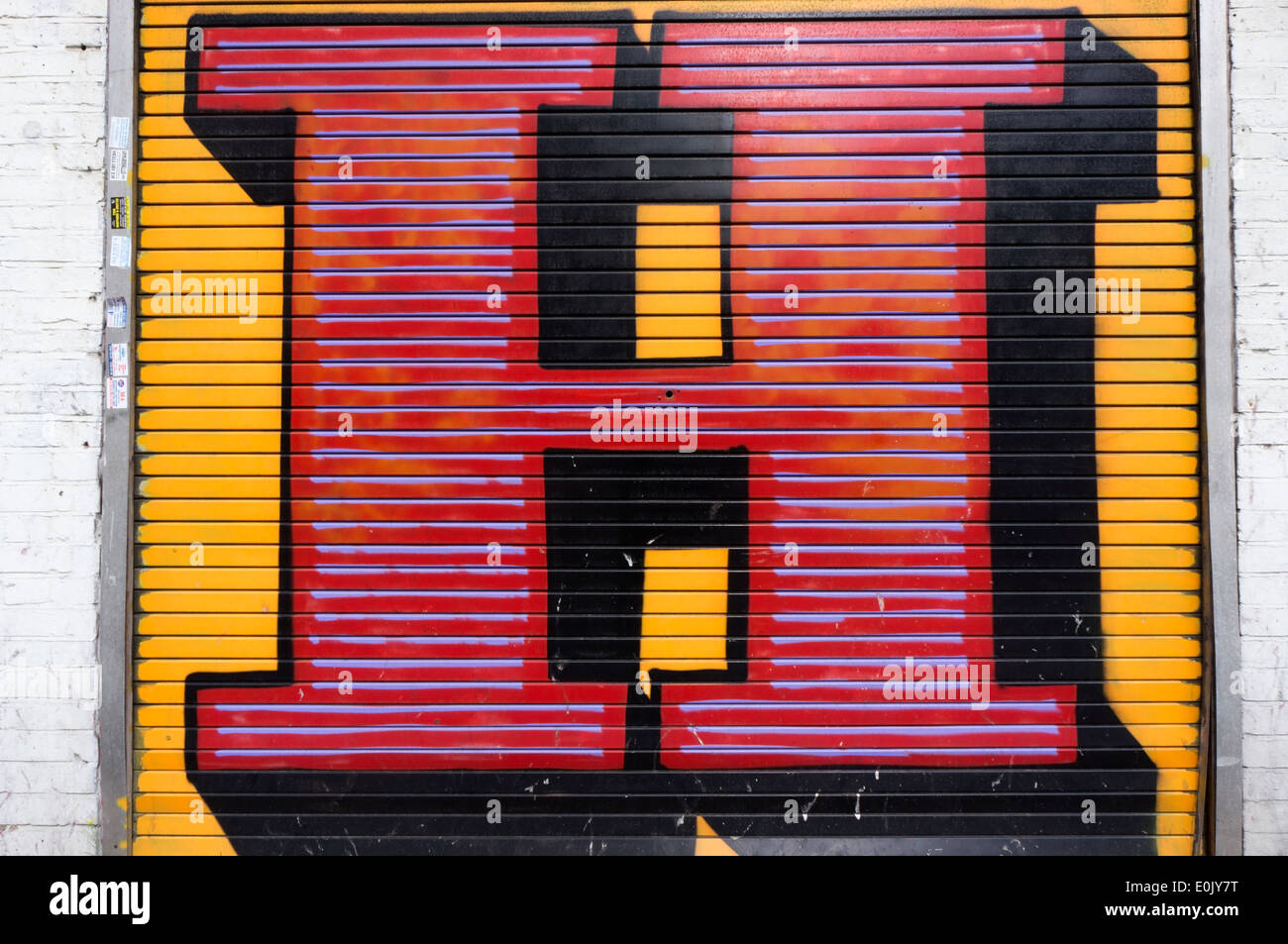A giant letter H painted on a roller shutter in Middlesex Street, London, by street artist Ben Eine. - Stock Image