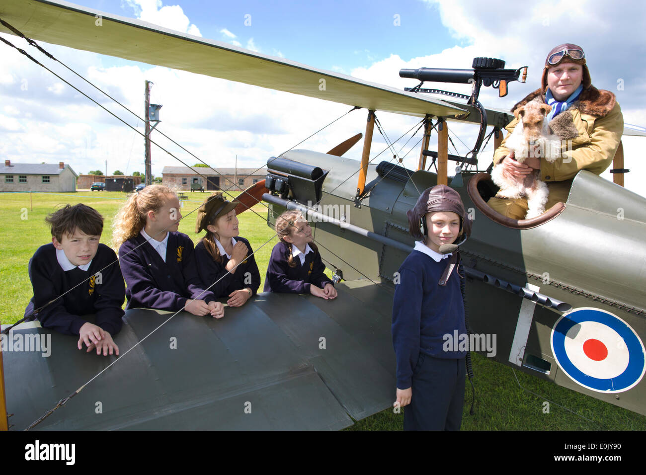 Stow Maries Aerodrome, UK. 14th May, 2014. Commemoration of Edgar Roberts WWI Royal Flying Corps Pilot accompanied on his fighter pilot missions by his terrier Mersea Mick Picture shows pupils (l-r) Ben Rumble, Zoe Clegg, Alannah Murrel, Amber Jones and Cameron Hope (wearing memorabilia hat) from the Mersea Island School visiting Stow Maries Aerodrome gathered around a SE5a replica WWI aorplane alongside pilot (Trevor Poole). Credit:  Clickpics/Alamy Live News - Stock Image