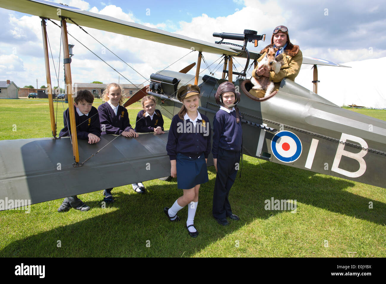 Stow Maries Aerodrome, UK. 14th May, 2014. Commemoration of Edgar Roberts WWI Royal Flying Corps Pilot accompanied on his fighter pilot missions by his terrier Mersea Mick Picture shows pupils (l-r) Ben Rumble, Zoe Clegg, Amber Jones, Alannah Murrel and Cameron Hope (wearing memorabilia hat) from the Mersea Island School visiting Stow Maries Aerodrome gathered around a SE5a replica WWI aerorplane alongside pilot (Trevor Poole). Credit:  Clickpics/Alamy Live News - Stock Image