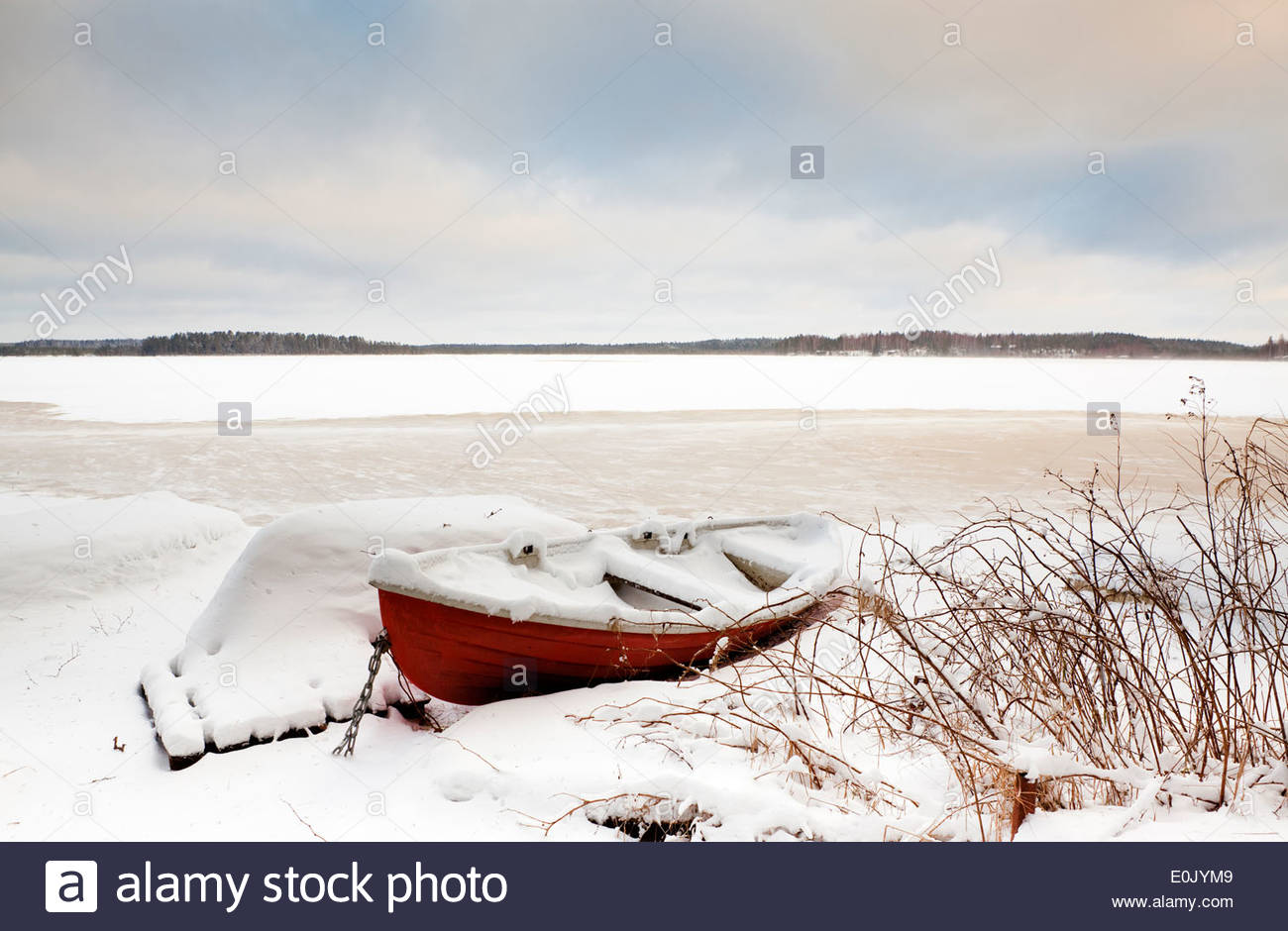 Boat on shore in winter - Stock Image