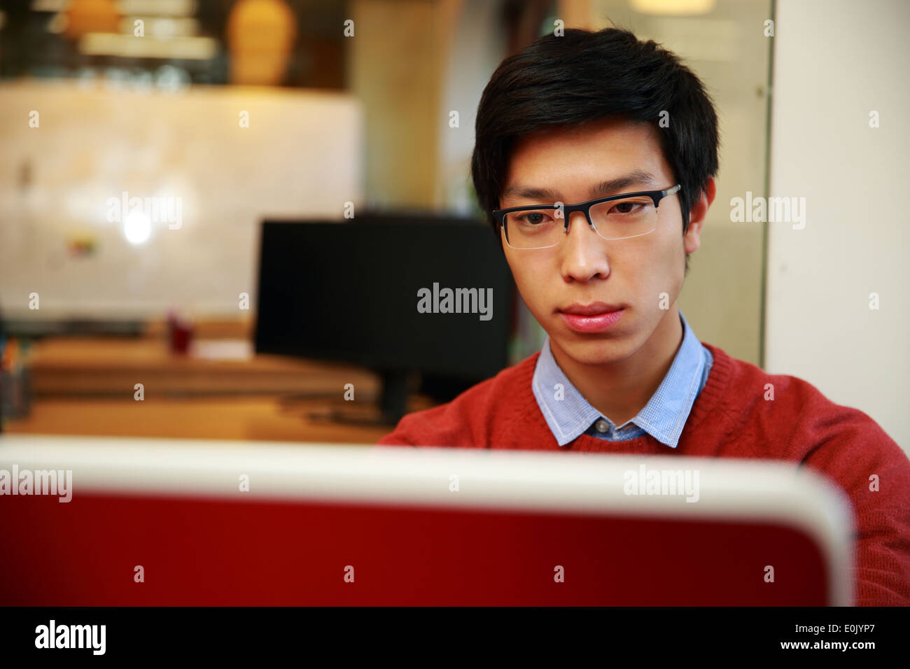 Young asian man in glasses working on laptop - Stock Image
