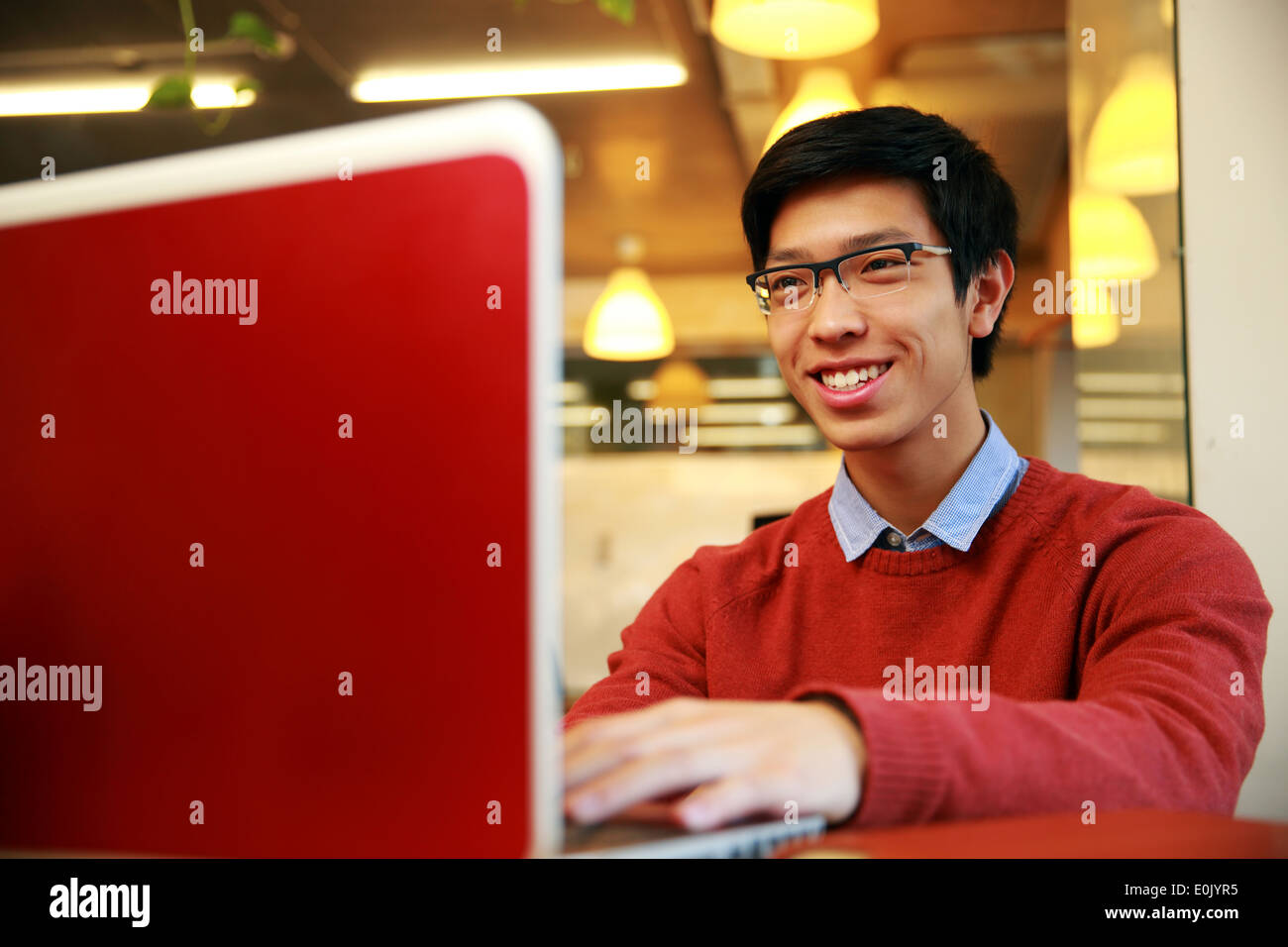 Cheerful young asian man using laptop - Stock Image