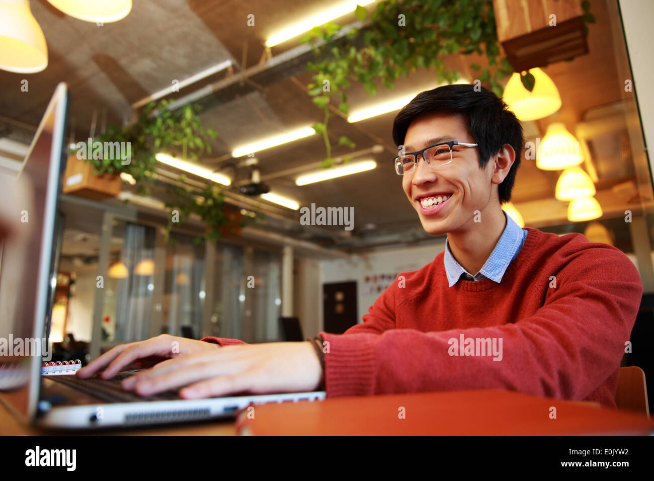 Cheerful asian man in glasses typing on laptop in office - Stock Image