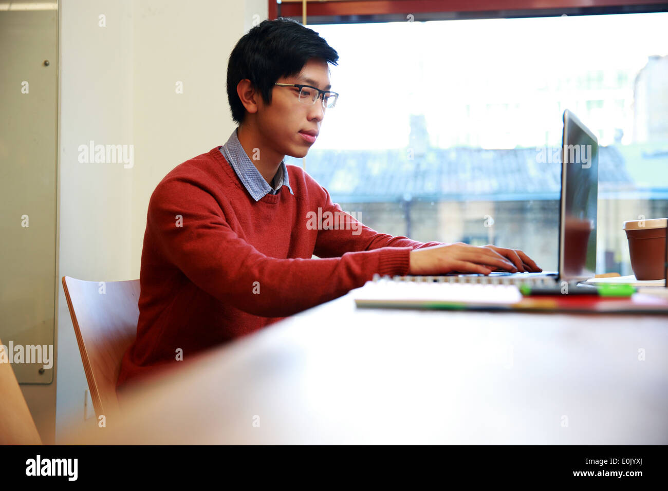 Smart asian man in glasses working on laptop in office - Stock Image