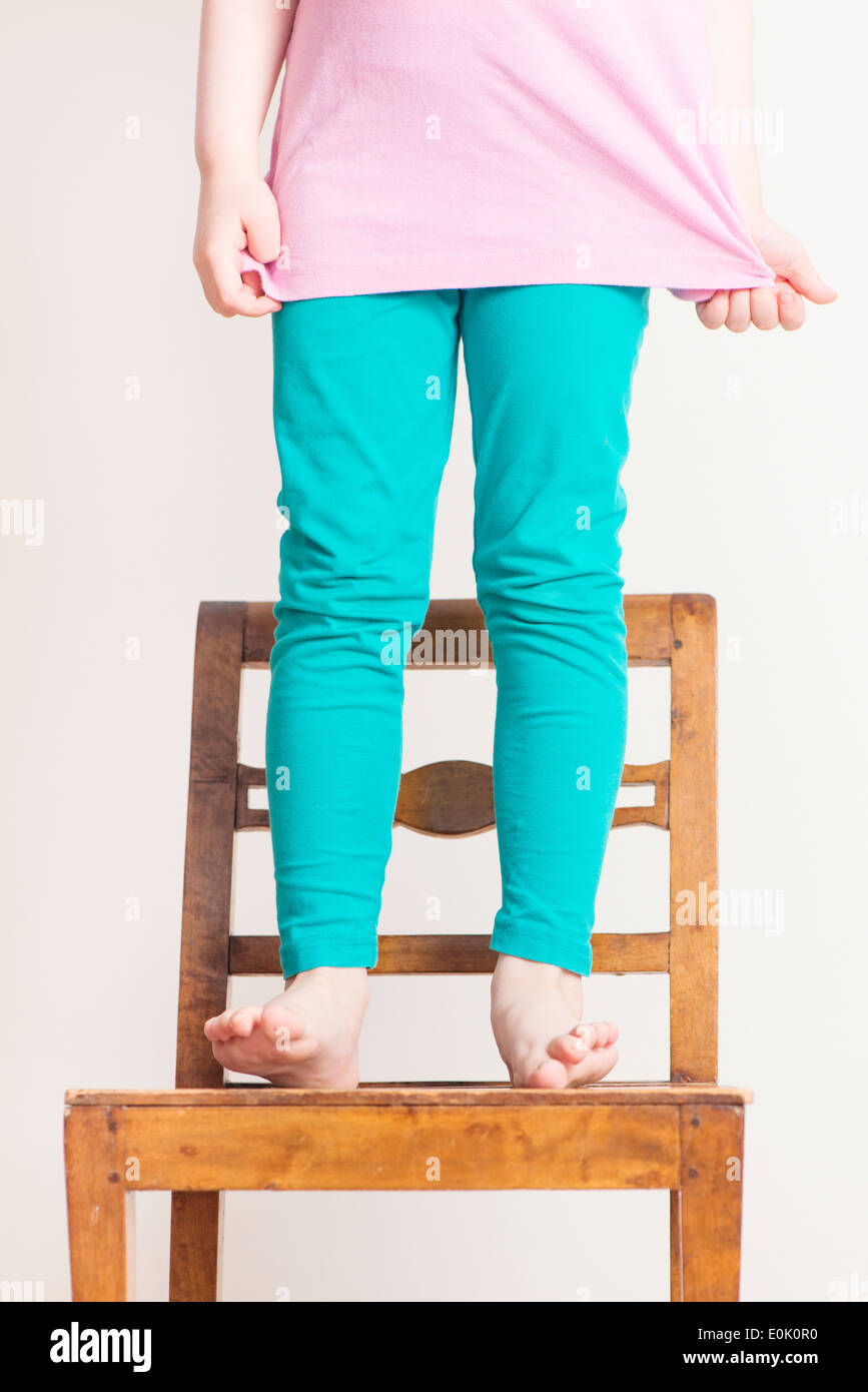 Little girl, 4 years old, standing with bare feet on a small wooden chair. - Stock Image