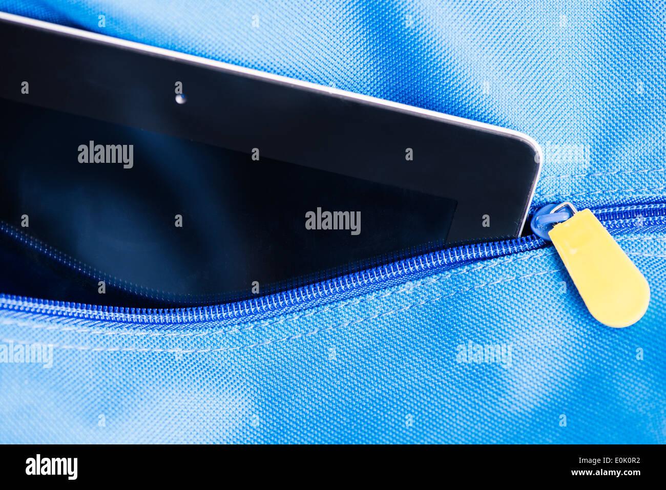 Digital tablet computer in blue school bag - Stock Image