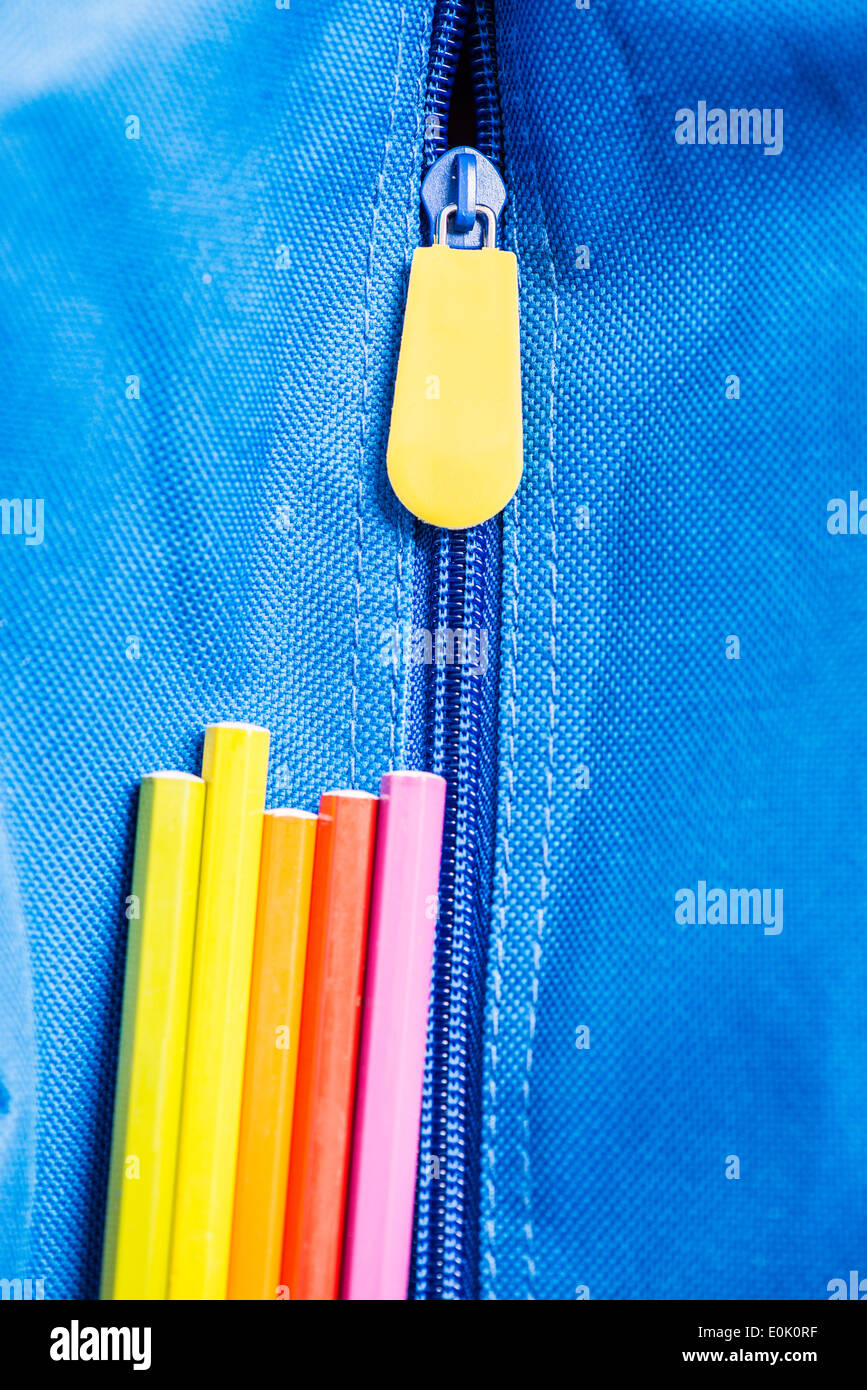 Colorful pens on blue school bag - Stock Image