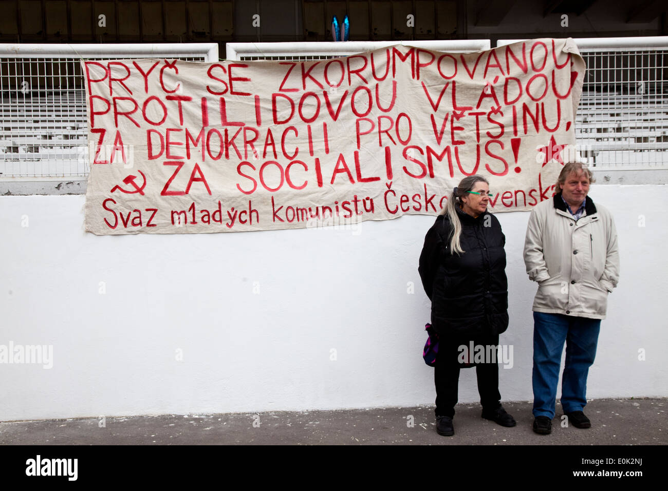 Czechs stand in front of a Czech Young Communist Union billboard urging to get rid of the current anti-people Czech - Stock Image