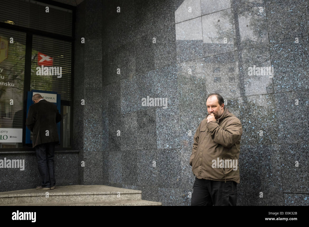 A man in front of a bank and ATM - Stock Image