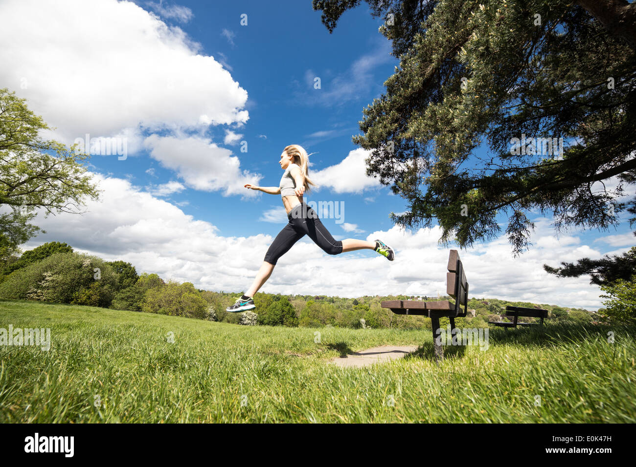 Blonde lady wearing black leggings and a grey crop top leaping from a bench on hampstead heath in the sunshine. - Stock Image