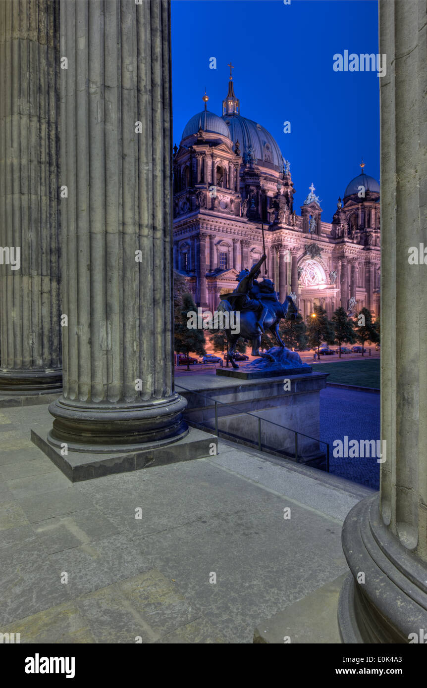 The Berlin Cathedral (Berliner Dom) through the columns of the Altes Museum at night. - Stock Image