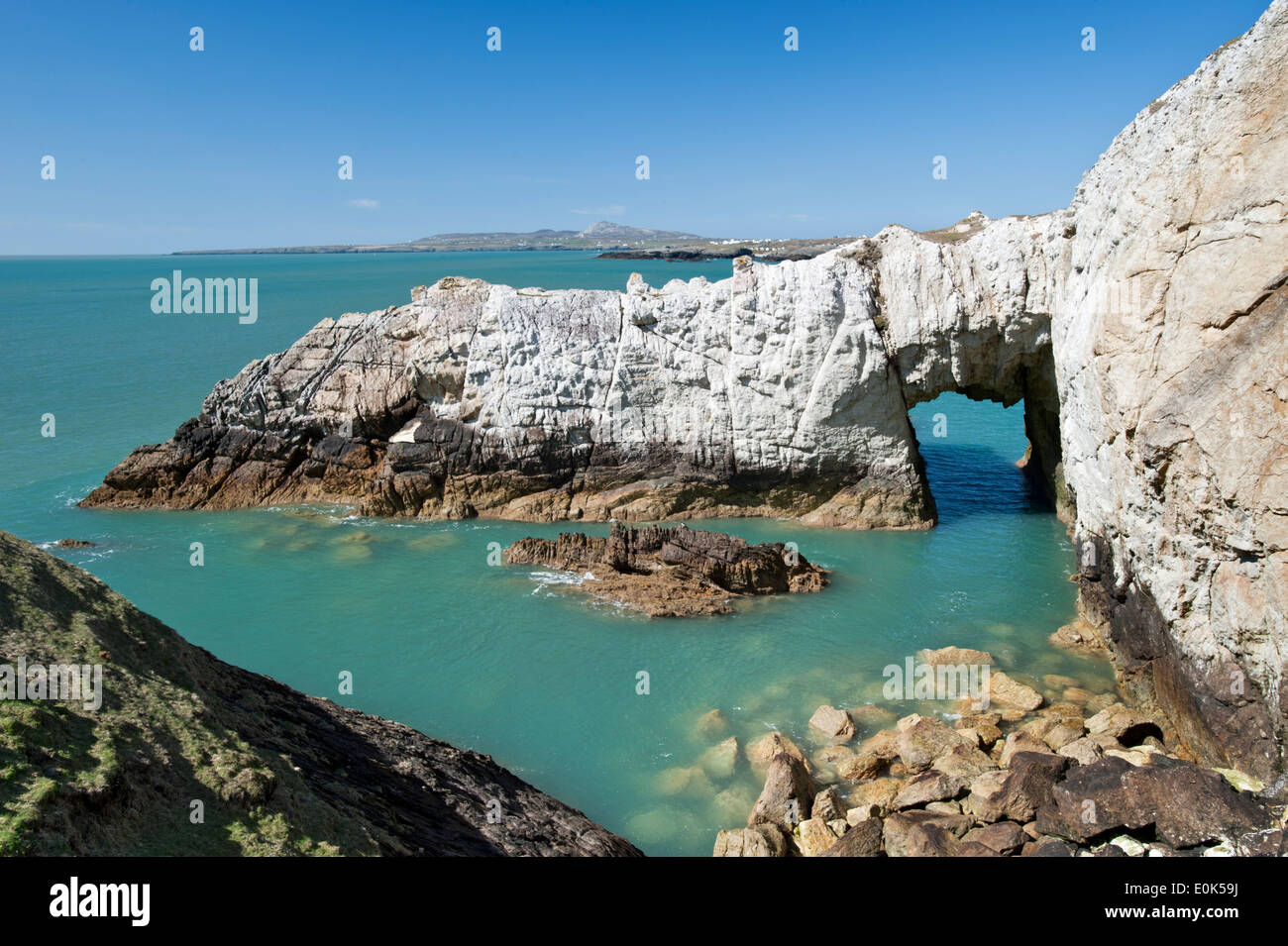 Bwa Gwyn white natural rock sea arch on coast, near Rhoscolyn, Anglesey, North Wales, UK - Stock Image