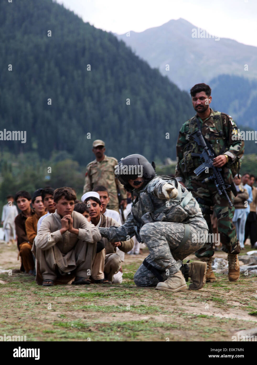 Local Pakistani kids await to be evacuated on a CH-60 Blackhawk in Khyber - Pakhtunkhwa, Pakistan, Sept. 13. The Stock Photo