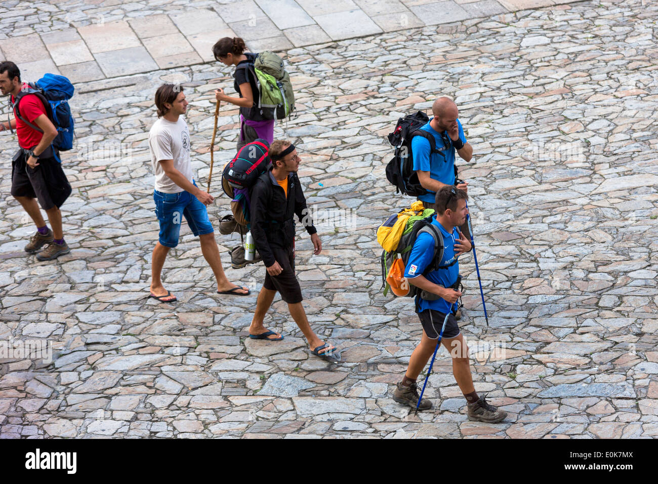 Pilgrims with walking poles end pilgrimage Camino de Santiago in Cathedral square of Santiago de Compostela, Galicia, Spain - Stock Image
