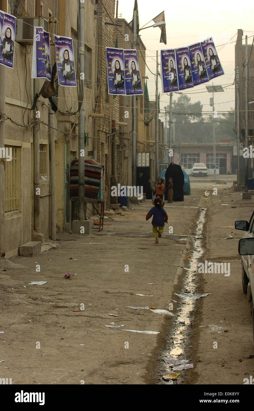 An Iraqi little girl runs underneath campaign posters for a