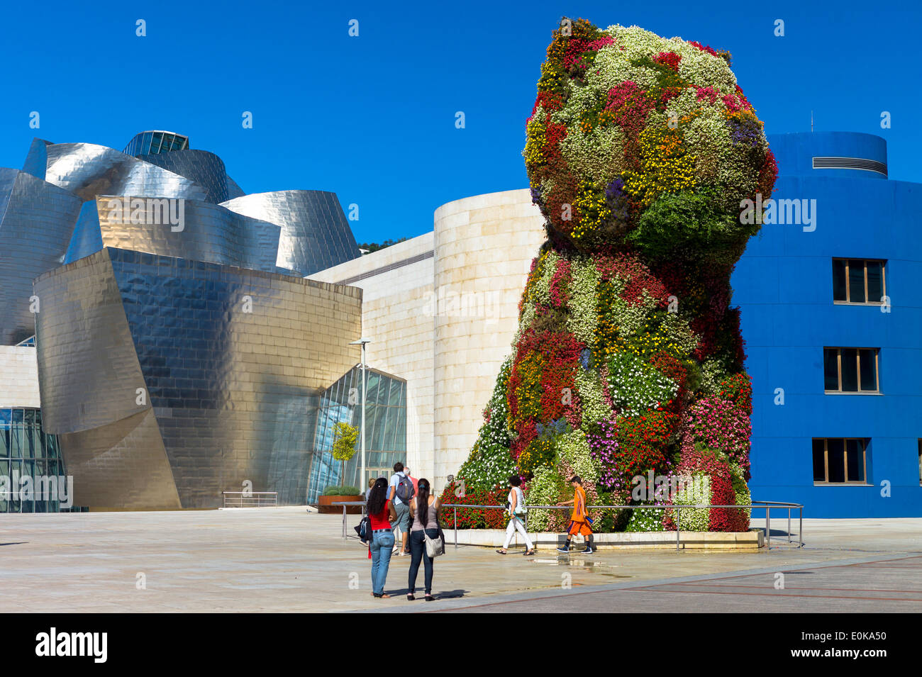 Tourists view Puppy flower feature floral art by Jeff Koons at Guggenheim Museum in Bilbao, Basque Country, Spain - Stock Image