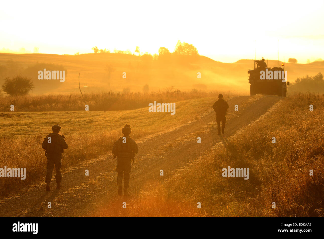 U.S. Army Europe soldiers of the 2nd Cavalry Regiment, patrol a road at the Grafenwoehr Training Area at sunrise during Saber J - Stock Image
