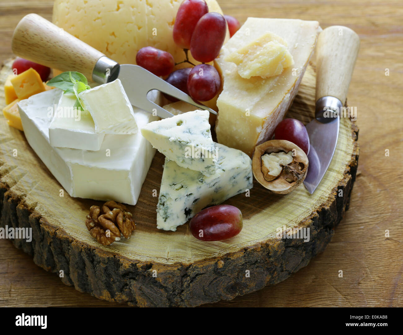 cheeseboard with assorted cheeses (parmesan, brie, blue, cheddar) - Stock Image