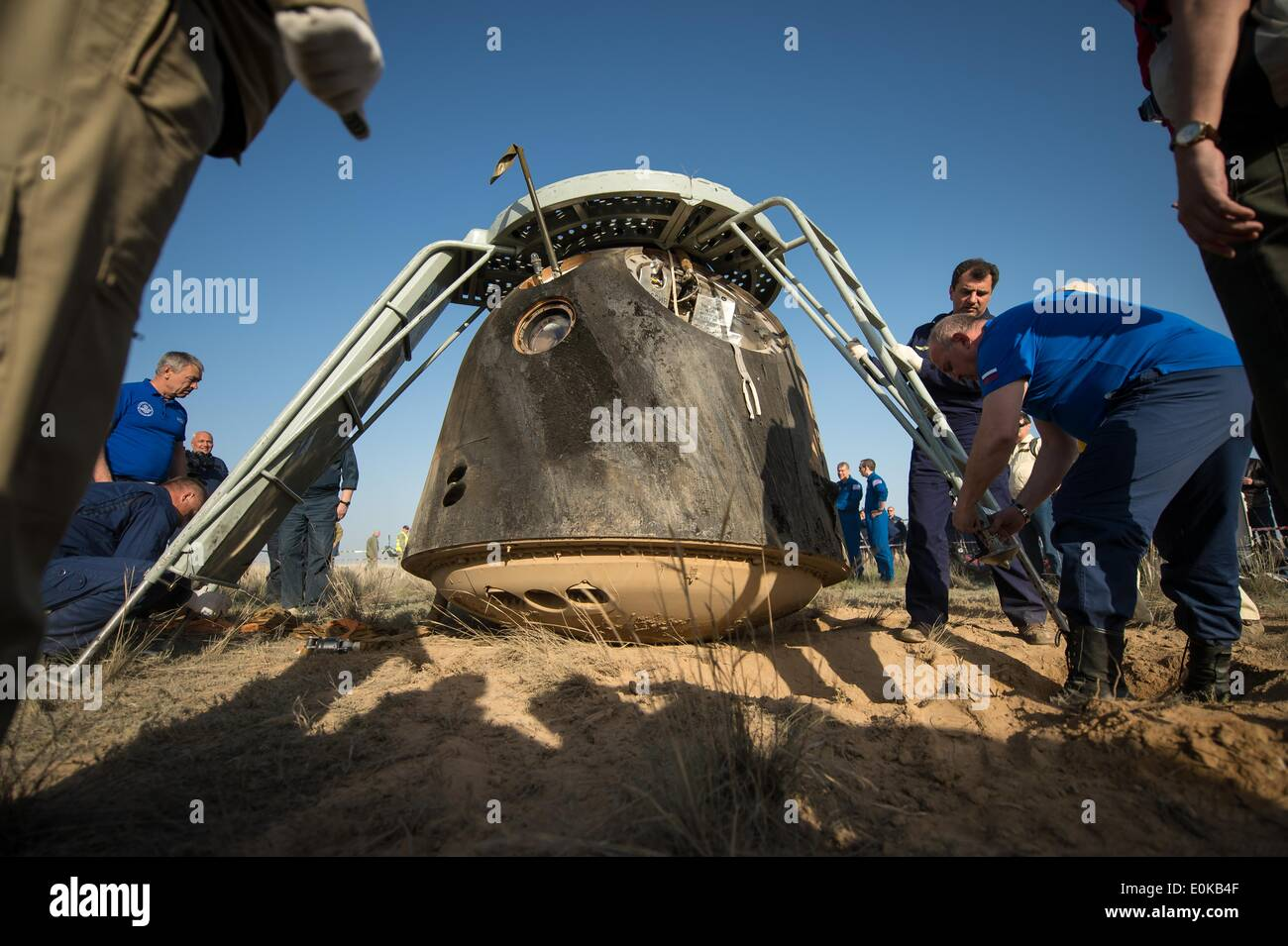 Support personnel prepare to exact the crew from the Soyuz TMA-11M spacecraft shortly after it landed carrying ISS Expedition 39 crew members May 14, 2014 near the town of Zhezkazgan, Kazakhstan. Wakata, Tyurin and Mastracchio returned to Earth after more than six months onboard the International Space Station where they served as members of the Expedition 38 and 39 crews. - Stock Image