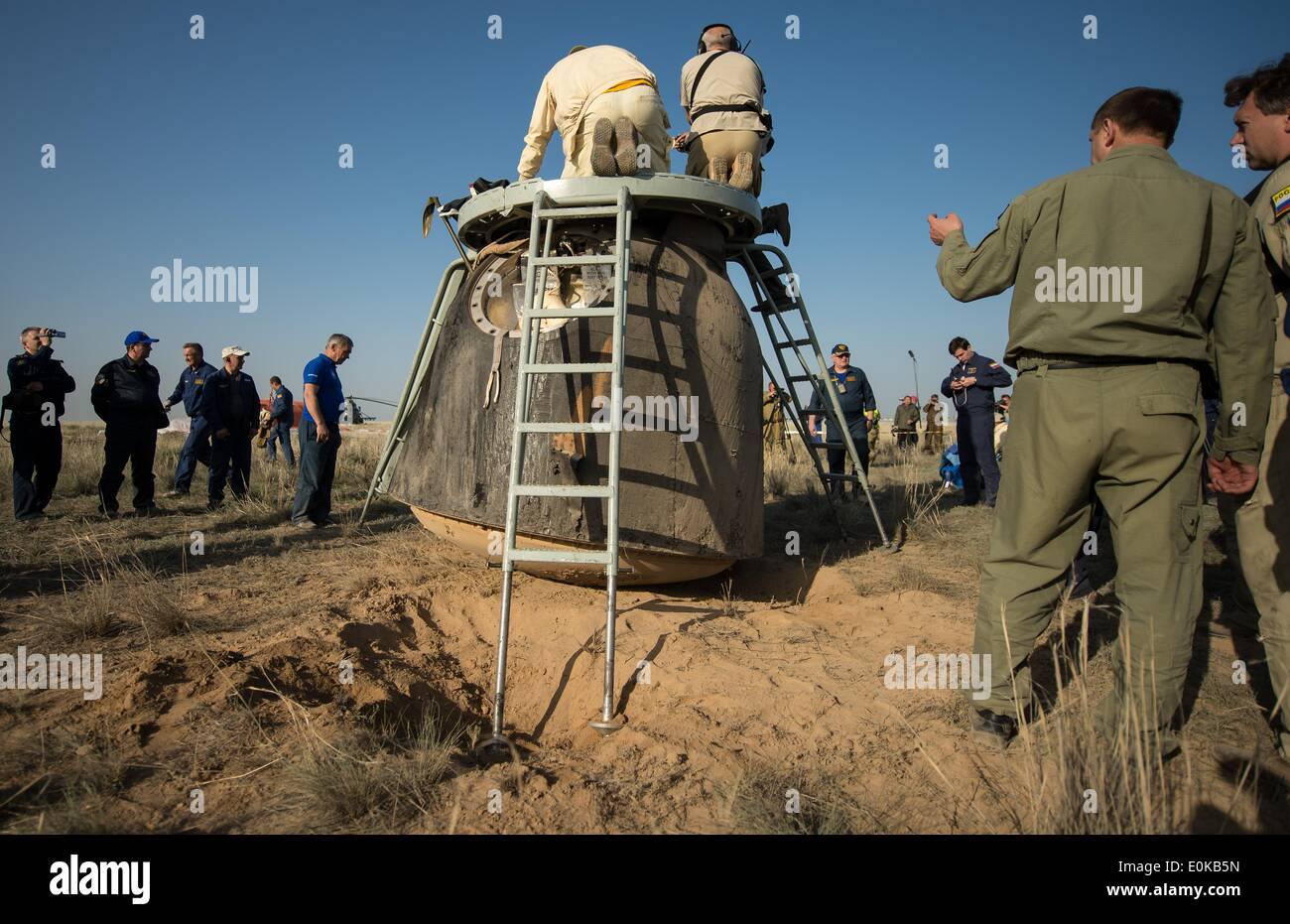 Support personnel prepare to extract the crew from the Soyuz TMA-11M spacecraft shortly after it landed carrying ISS Expedition 39 crew members May 14, 2014 near the town of Zhezkazgan, Kazakhstan. Wakata, Tyurin and Mastracchio returned to Earth after more than six months onboard the International Space Station where they served as members of the Expedition 38 and 39 crews. - Stock Image