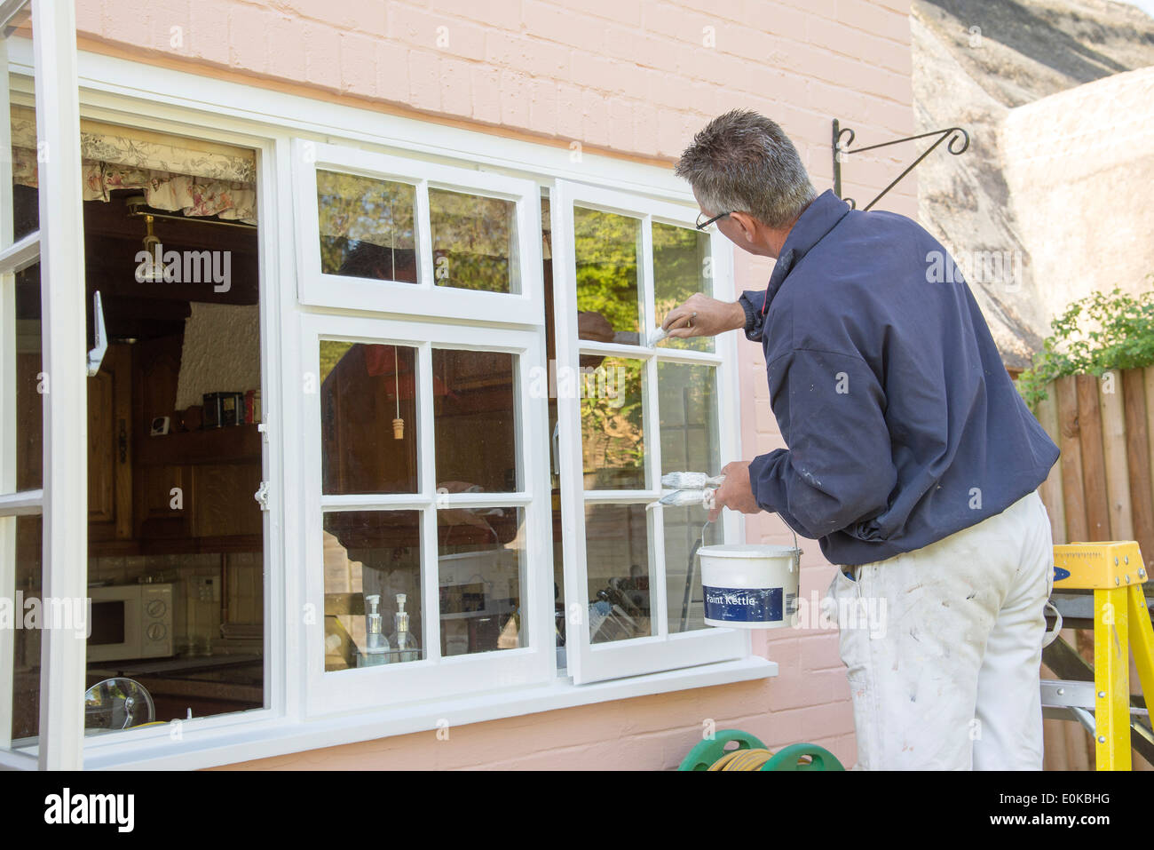 Professional painter decorator painting a thatched cottage - Stock Image