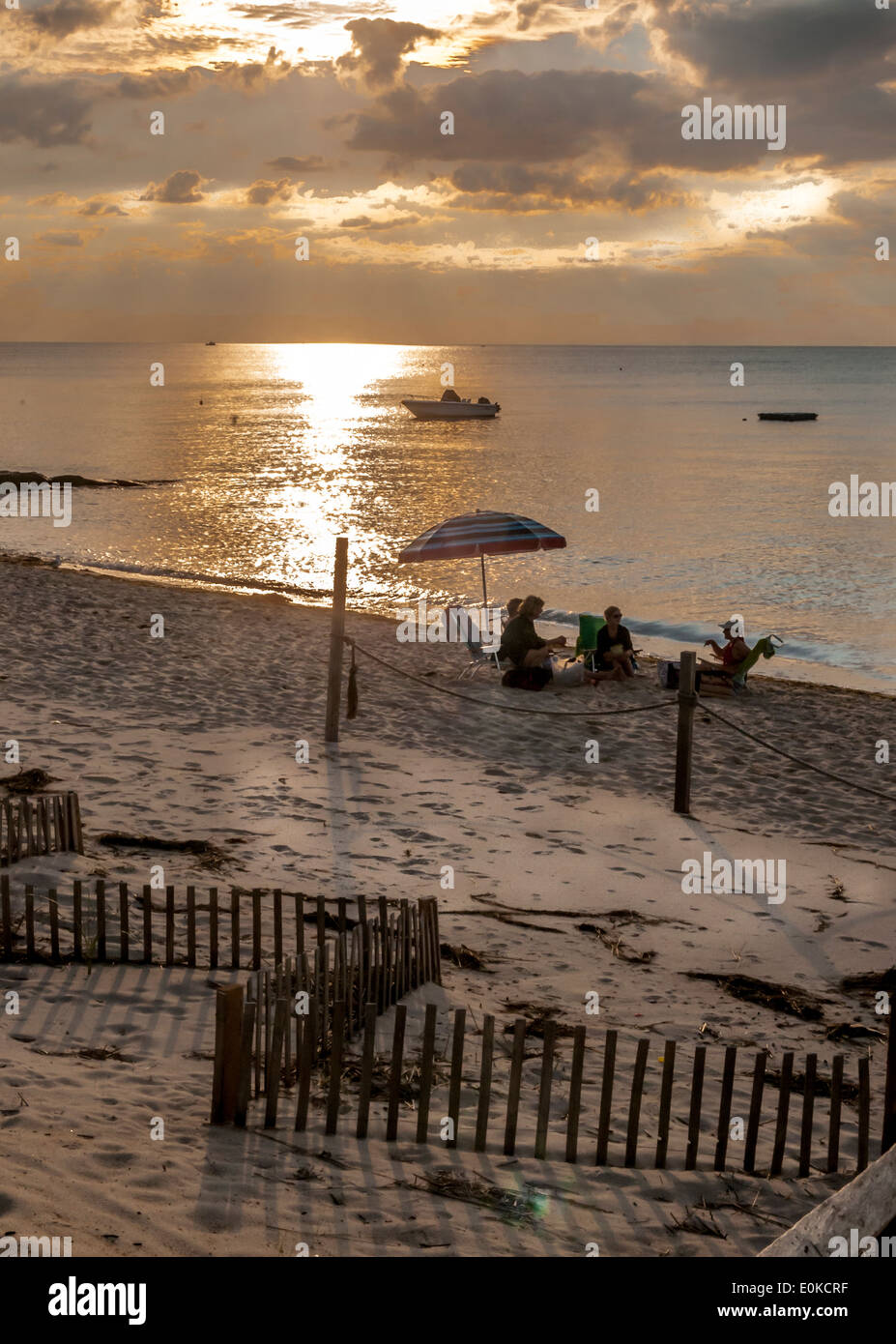 As the Sun begins to set friends sit enjoying the last warmth of the summer sun at Saint Landing Brewster, Ma.,U.S.A. Stock Photo