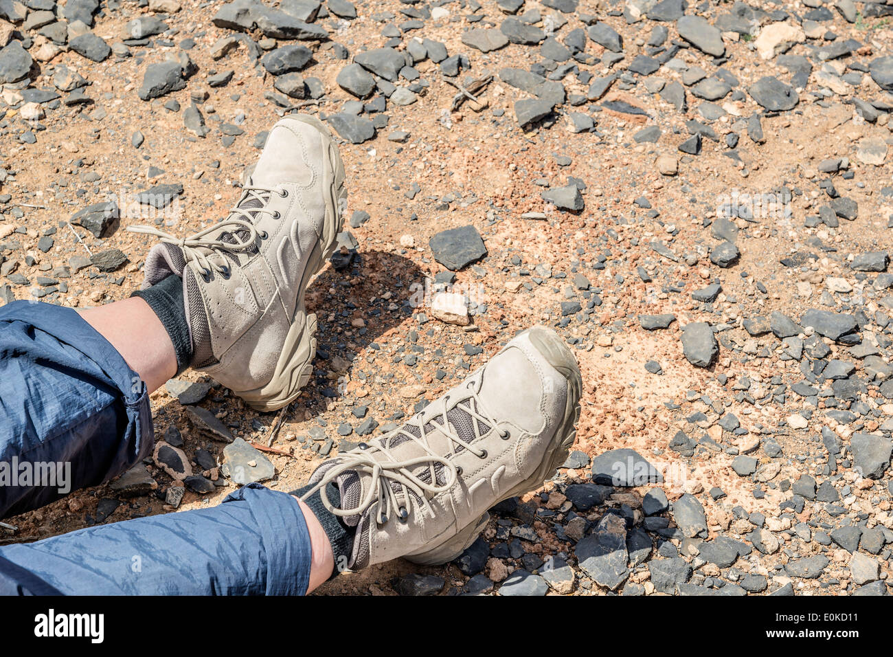 Closeup of tramping boots of a resting person on Jebel Shams Oman - Stock Image