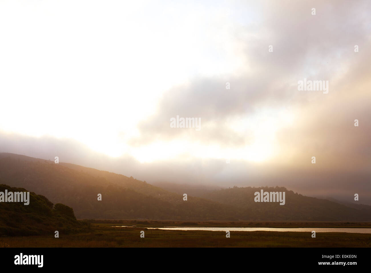 The sun sets over the foggy landscape with mountains in the distance and a body of water in the foreground. - Stock Image