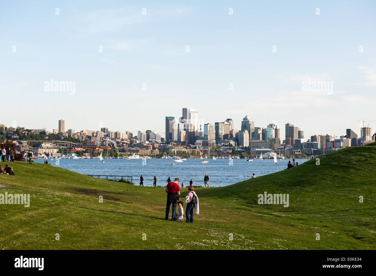 Families and friends gather at Gas Works Park which overlooks Lake Union and the Seattle Skyline. - Stock Image