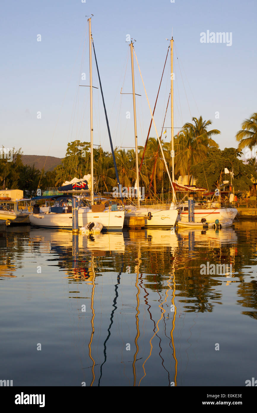 Sailboats docked at a yacht club reflect in the calm water at sunset. - Stock Image