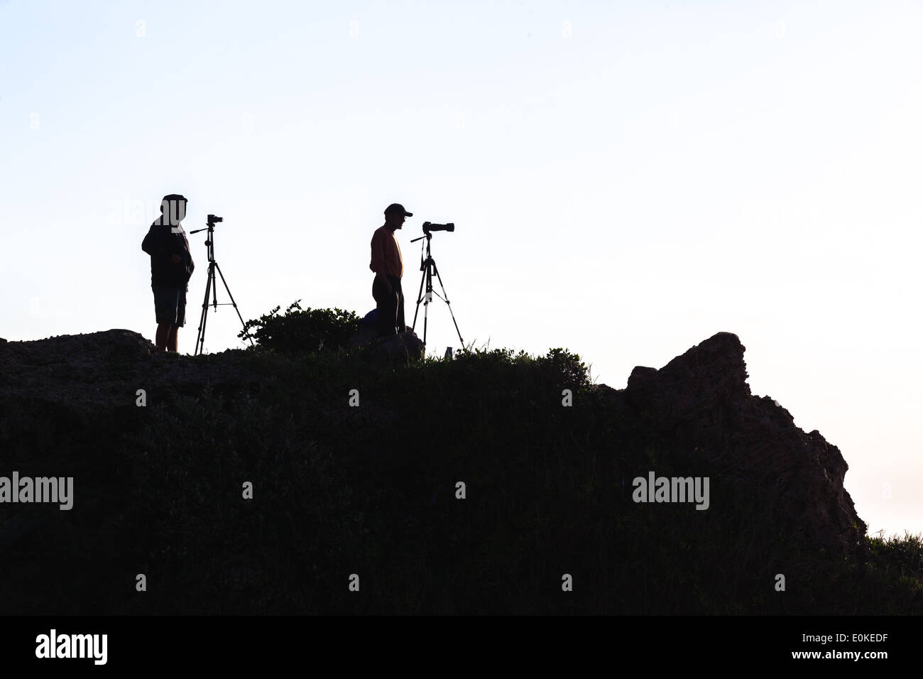 Silhouetted unidentified photographers on rocky headland - Stock Image