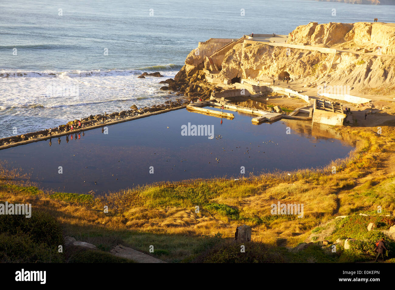 People walk in a single file line along the sea wall at the Sutro Bath Ruins at Lands End in San Francisco, California. - Stock Image