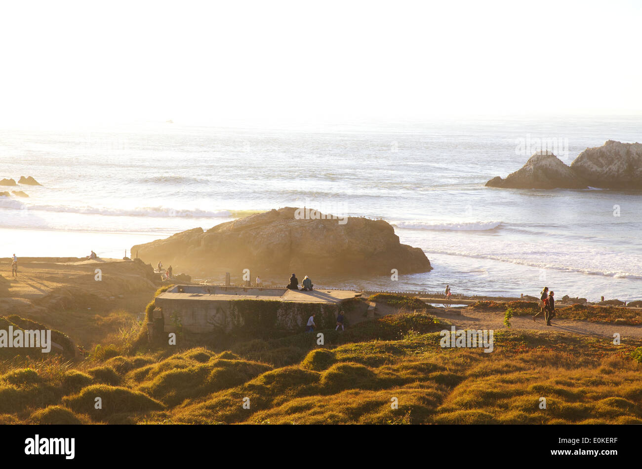 People enjoy the sunshine and walk around at the waterfront at the Sutro Baths at Lands End in San Francisco, California. - Stock Image