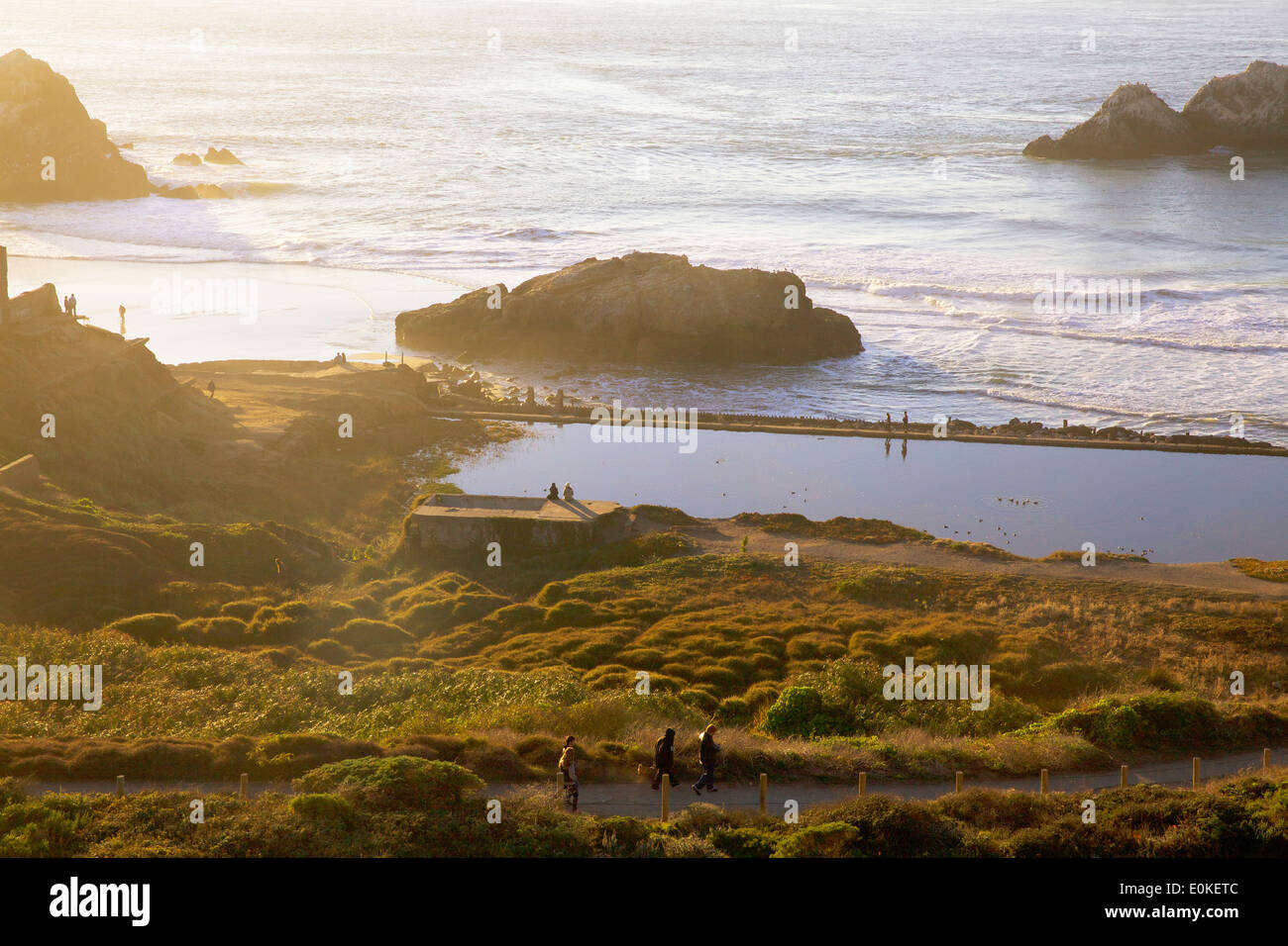 People hike around on the paths and walk along the sea wall at the Sutro Bath Ruins at Lands End in San Francisco, California. - Stock Image