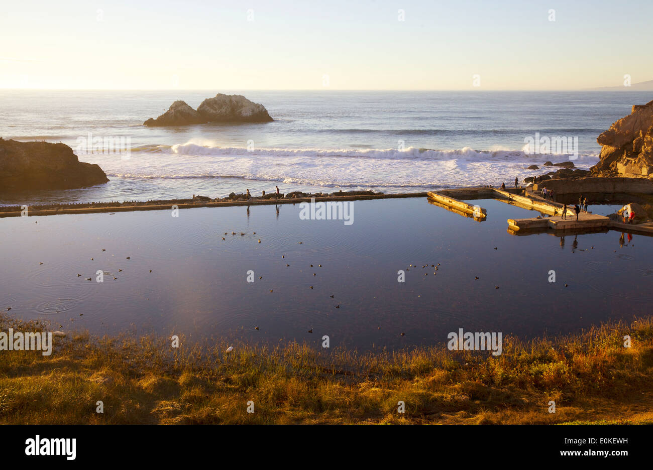 People walk along the sea wall at the Sutro Bath Ruins at Lands End in San Francisco, California. - Stock Image