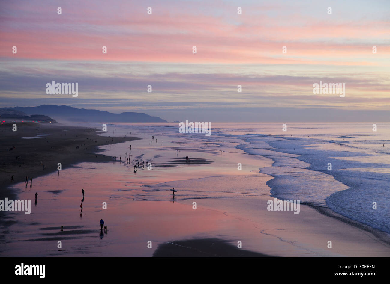 People walking along the shore are silhouetted against a brilliant sunset with colors of blue, pink and purple. - Stock Image
