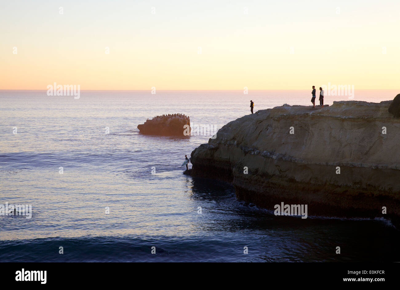 Onlookers watch on a cliff at sunset as a surfer prepares to jump into the ocean at Steamers in Santa Cruz California. - Stock Image