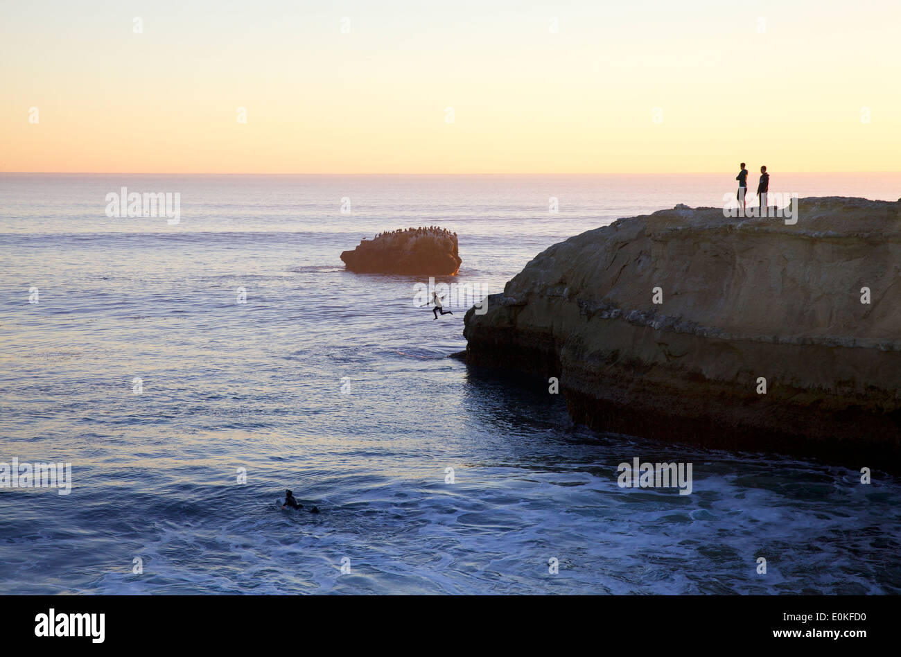 Onlookers watch on a cliff as a surfer jumps into the ocean at Steamers in Santa Cruz California at sunset. - Stock Image