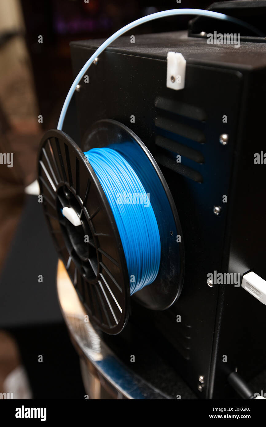 Spool of plastic thread feeding in to a 3D printer - Stock Image