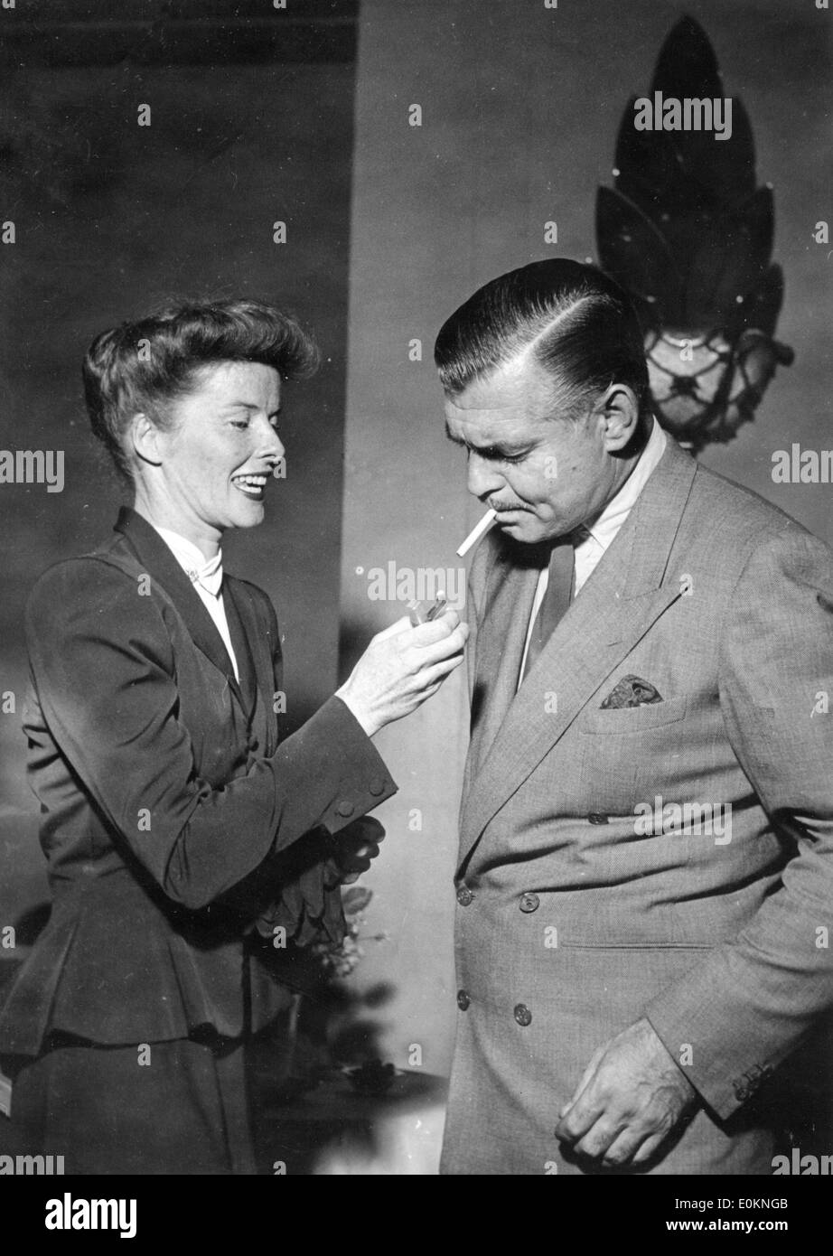 Actress Katharine Hepburn lighting a cigarette for Clark Gable - Stock Image
