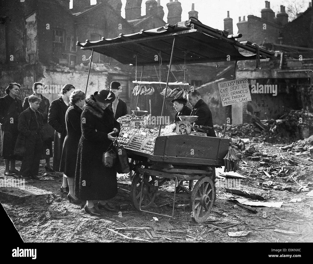 People buying food from a street cart among wreckage from the Blitz - Stock Image