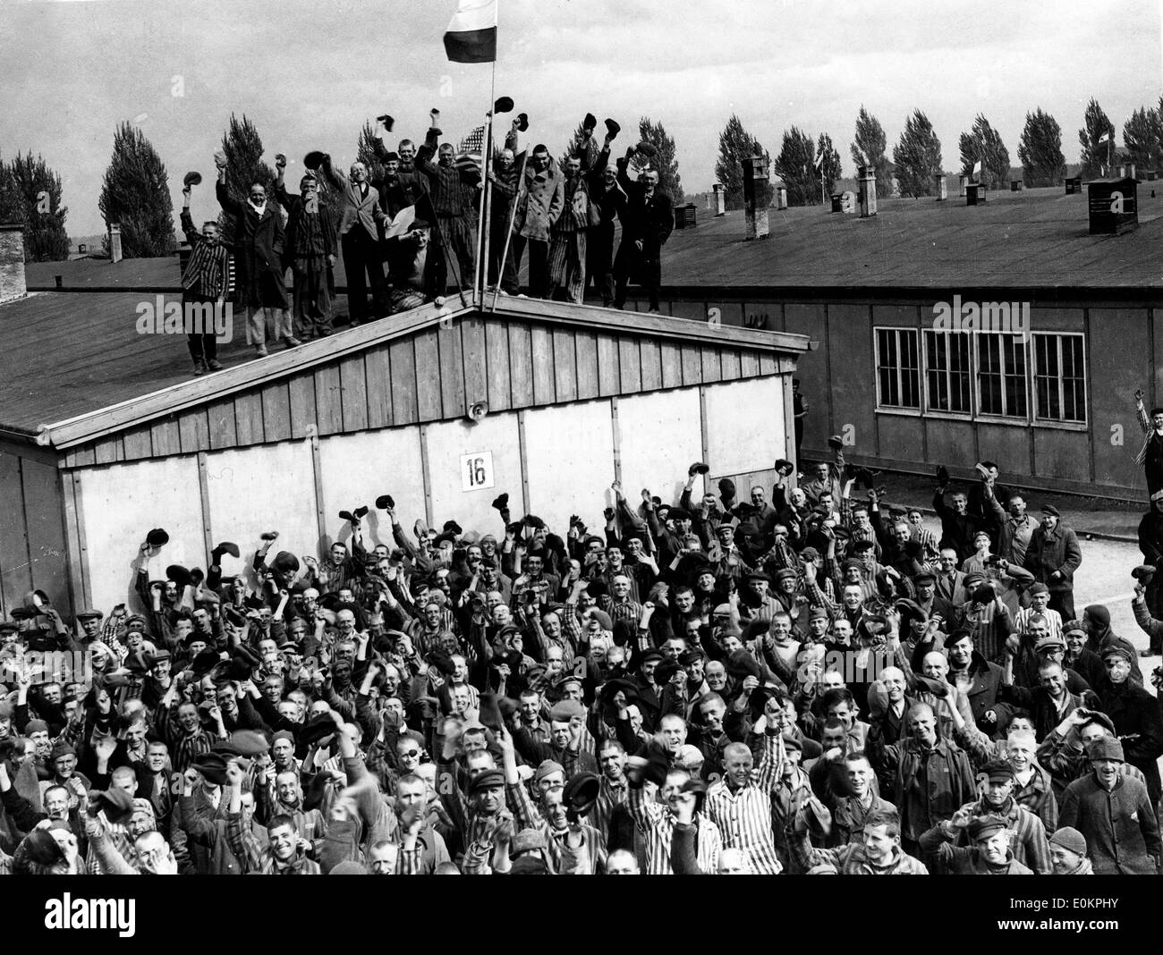Political prisoners cheer madly as they hear guns of the 42nd Rainbow Division as they approach Dachau - Stock Image