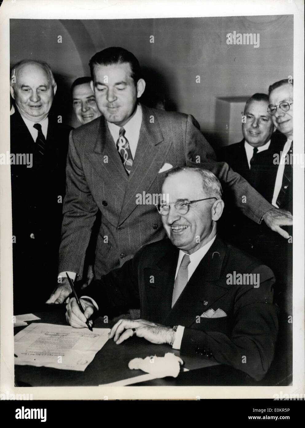 May 05, 1946 - More Money For Postal Employees: Washington, D.C. President Harry S. Truman affixes his signature to the postal pay raise bill in Washington, D.C., May 21, as Postmaster General Robert E. Hannegan looks on in the presence of other postal officials, rear. It gives all postal employees a raise of 00 per year and corrects cetain losses incurred when the 10% increase last year eliminated overtime. - Stock Image