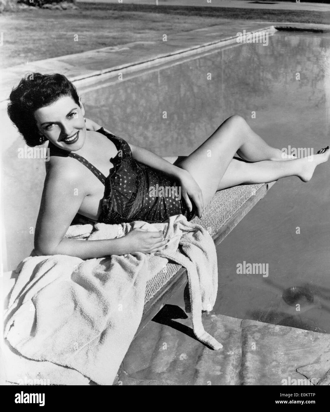 f246aef178ad3 Actress Jane Russell laying on the diving board by her pool - Stock Image