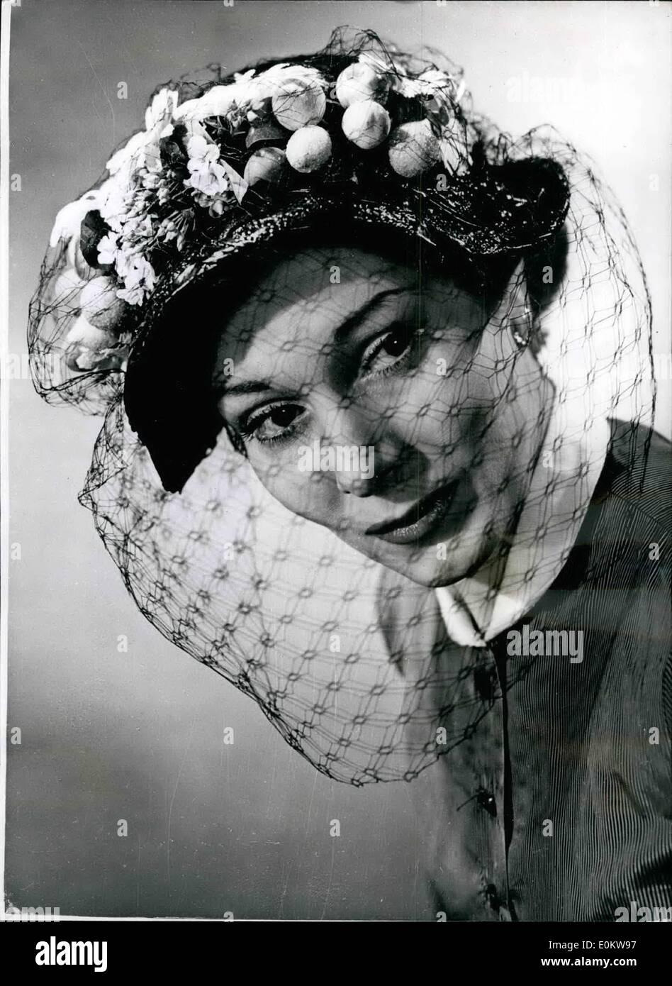 Apr. 04, 1950 - Garlanded with Fruit and Flowers Charming spring Hat style. Photo Shows A Garland of Fruit and Flowers forms the Decoration for this Striking Fancy black straw bonnet. A black veil completes the effect. - Stock Image