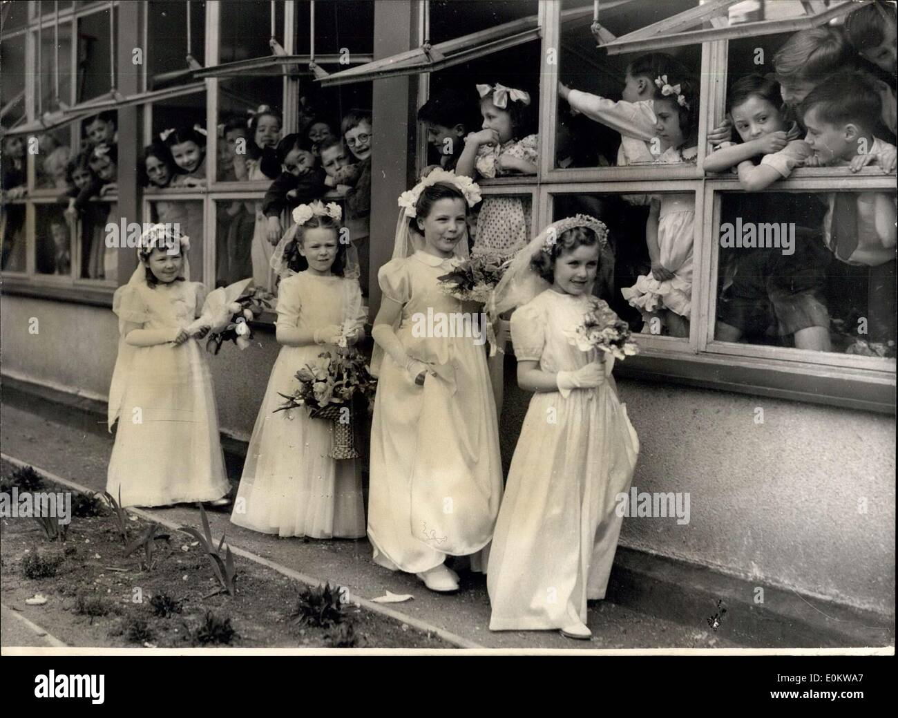 May 02, 1950 - May Day ceremonies at the Hugh Eyddleton School the Youngsters look on; Photo Shows Four of the tiny May Queen's - Stock Image